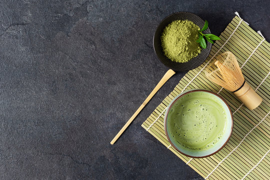 Green matcha tea drink and tea accessories on black background top view. Japanese tea ceremony concept.