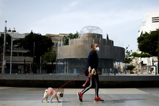 A woman wears a face mask as she walks with her dog in Tel Aviv amid the coronavirus disease (COVID-19) restrictions around Israel