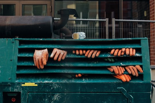 Close-up Of Orange Protective Gloves On Green Metallic Machinery