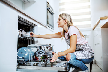 Beautiful caucasian blond housewife in apron crouching in front of dishwasher and putting dishes. Kitchen interior.