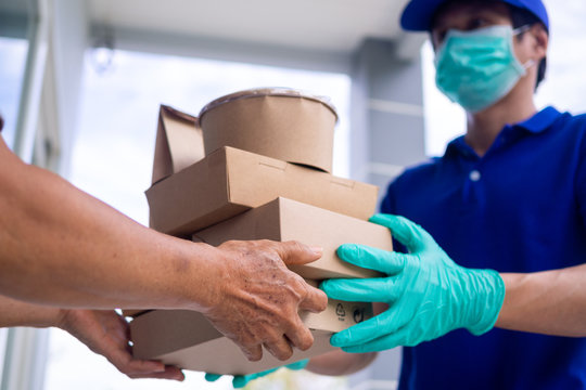 The shipper wears a mask and gloves, delivering food to the home of the online buyer. stay at home reduce the spread of the covid-19 virus. The sender has a service to deliver products or food quickly