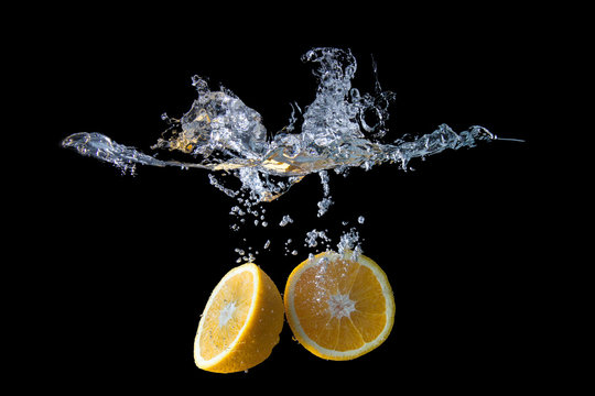 Close-up Of Lemons In Water Against Black Background