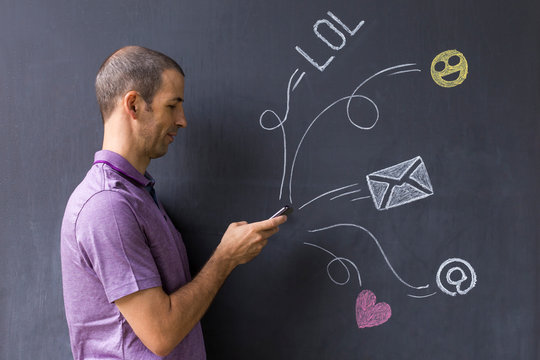 Side View Man Using Mobile Phone While Standing By Blackboard With Various Icons