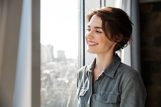Image of beautiful young joyful woman smiling and looking at window