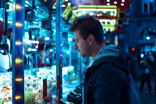 Side View Of Man Playing Toy Grabbing Game