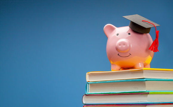 Piggy bank in graduate hat on stack of books. Blue background. Copy space for text