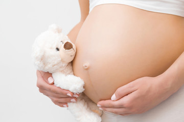 Obraz Hand holding smiling white teddy bear. Young woman naked belly. Emotional loving moment in pregnancy time - 30 weeks. Baby expectation. Love, happiness and safety concept. Closeup. Side view. - fototapety do salonu