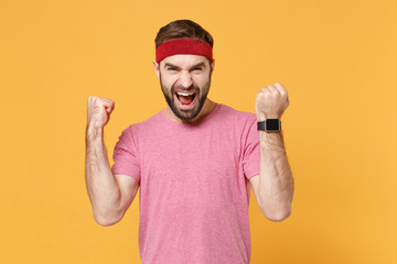 Screaming young bearded fitness sporty guy sportsman in headband t-shirt in home gym isolated on...
