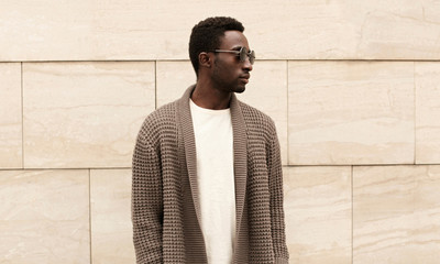 Wall Mural - Stylish african man looking away wearing brown knitted cardigan, sunglasses on city street over brick wall background
