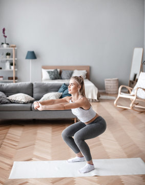 Fit woman in sportswear is doing squat exercises at home.