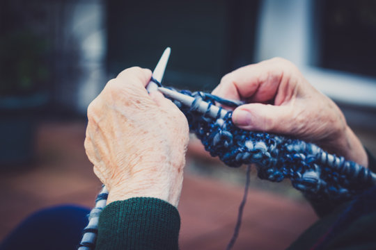 closeup on old lady hands to knitting