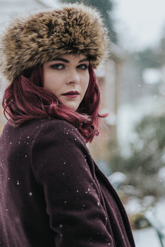 Close-up Portrait Of Young Woman In Warm Clothing Standing Outdoors