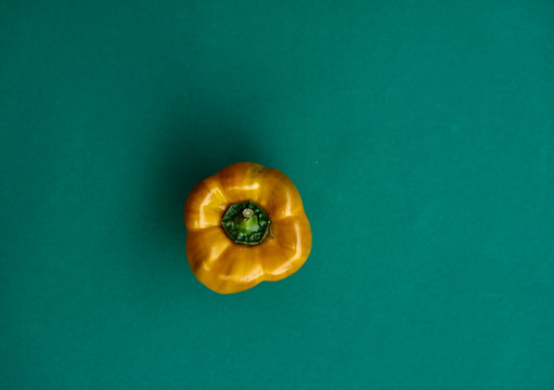 Close-up Of Yellow Bell Pepper Over Green Background