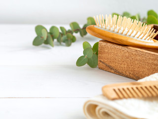 Hygienic bathroom and spa accessories on wooden table. Wooden hair brush and comb, towel and green leaves. Hair care at home.