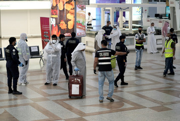 A Kuwaiti passenger holding his luggage walks by the police and civil aviation personnel upon his arrival from Amman at Kuwait Airport, in Kuwait City