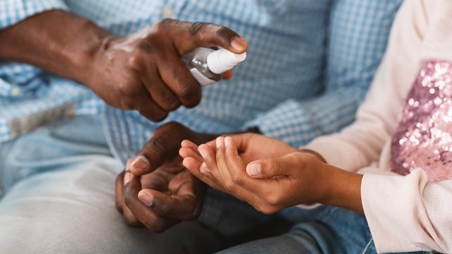 Hygiene during epidemic. Unrecognizable African American grandparent and his grandchild cleaning hands with sanitizer