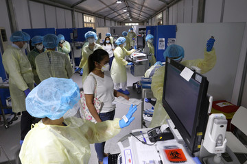 A woman waits to be tested by medical staff wearing protective equipment, amid the coronavirus disease (COVID-19) outbreak, at the Cleveland Clinic hospital in Abu Dhabi
