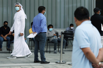 A member of hospital staff, wearing a protective face mask, watches over people queuing to be tested, amid the coronavirus disease (COVID-19) outbreak, at the Cleveland Clinic hospital in Abu Dhabi