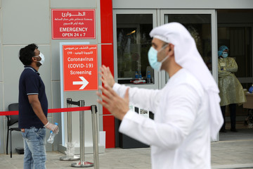 A hospital employee directs people waiting to be tested, amid the coronavirus disease (COVID-19) outbreak, at the Cleveland Clinic hospital in Abu Dhabi