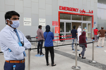 People wearing protective face masks wait to be tested, amid the coronavirus disease (COVID-19) outbreak, at the Cleveland Clinic hospital in Abu Dhabi