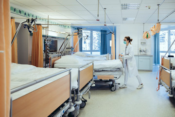 Doctor in hospital room pushing beds