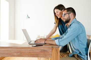Smiling couple working at laptop from home in home office in modern living room