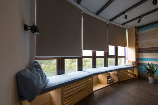 Motorized roller shades in the interior. Automatic roller blinds beige color on big glass windows. Remote Control Shades are above the windosill with pillows. Summer. Green trees outside.