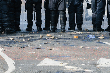 Stones and bricks litter the road as police riot squad move forward after a crowd riots