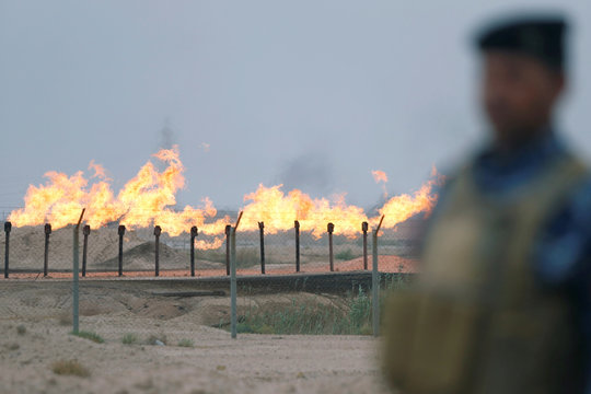 Member of the Iraqi security forces stands guard at an oil burner in al-Zubair oil field, near Basra