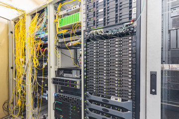 Powerful computing hardware works in the data center racks. Central technical platform of the Internet provider. There is a lot of telecommunications equipment in the server room.