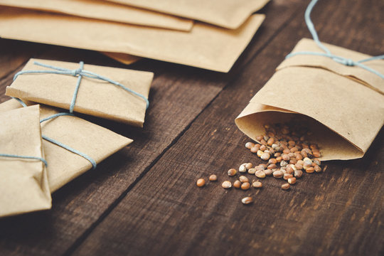 Paper bags with seeds for planting. Sprinkled radish seeds. Wooden table.