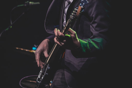 Midsection Of Man Playing Electric Guitar On Stage