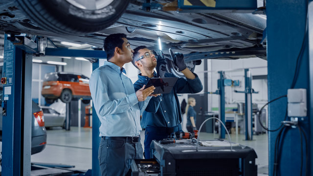 Manager Checks Data on a Tablet Computer and Explains the Breakdown to a Mechanic. Car Service Employees Inspect the Bottom of the Car with a LED Lamp. Modern Clean Workshop.