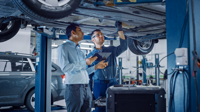 Manager Checks Data on a Tablet Computer and Explains the Breakdown to a Mechanic. Car Service Employees Inspect the Bottom and Skid Plates of the Car. Modern Clean Workshop.