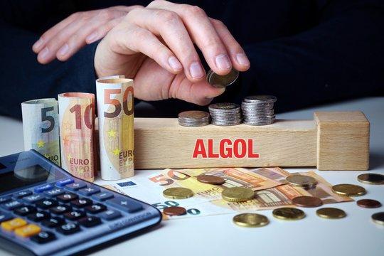 ALGOL. Mann stapelt Geld (Euro). Begriff ALGOL auf Baustein. Münzen, Scheine & Taschenrechner. Konzept für Business, Finanzen, Wirtschaft