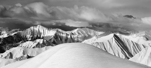 Fototapete - Black and white  off-piste snowy slope and cloudy mountains