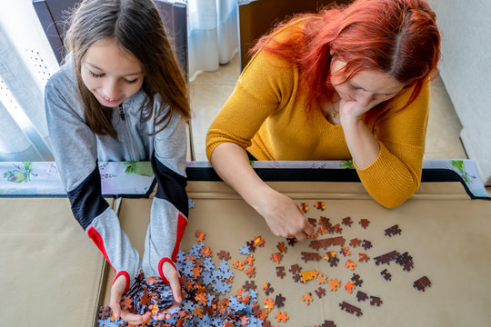 Mother and daughter doing puzzle in the living room at home