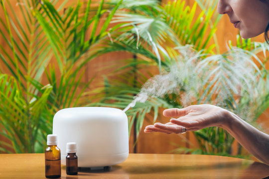 Woman Enjoying Aroma Therapy Steam Scent from Home Essential Oil Diffuser or Air Humidifier