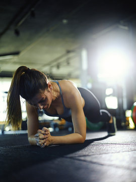 Backlit vertical shot of exhausted young woman doing forearm plank exercise during workout in gym
