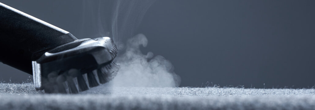Home cleaning. Steam carpet cleaning on a grey background. Photo from copy space.