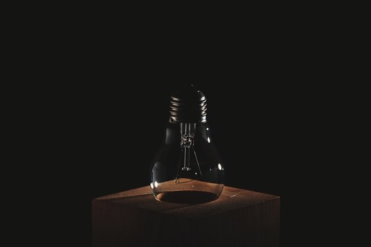 Close-up Of Light Bulb On Table Against Black Background