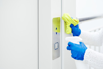 Close up hand of woman disinfecting lift push