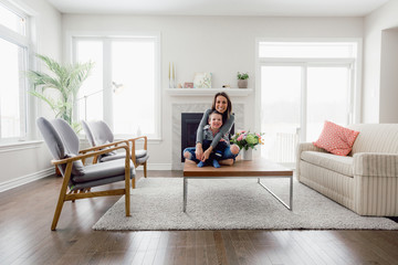 Young mother and son sitting on coffee table in living room - wide shot