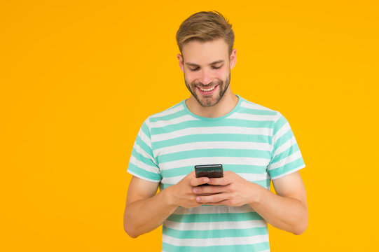 Texting SMS message. Happy guy send sms via smartphone yellow background. Sms messaging. Short message service. New technology. Mobile lifestyle. Modern life. Trusted SMS delivery