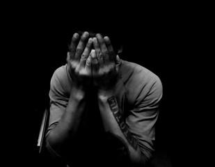 Depressed Man Covering Face Against Black Background