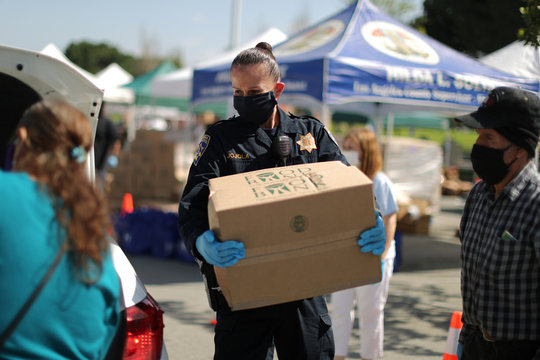 Volunteers at Los Angeles Food Bank hand out supplies at a drive-through food giveaway as the global outbreak of coronavirus disease (COVID-19) continues, in Los Angeles