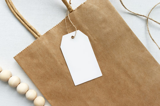 Blank white gift luggage tag on a brown paper bag - Flat lay gift tag mockup