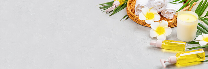 Spa massage Aromatherapy body care background. Spa herbal balls, cosmetics, towel and tropical leaves on gray concrete table. Top view, flat lay, overhead, copy space. Beauty and health care concept