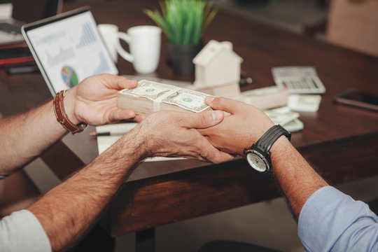 Cropped Hands Of Man Giving Money To Colleague In Office