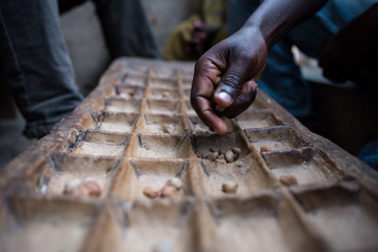 african man hand playing mancala, traditional game on wooden board with pebbles